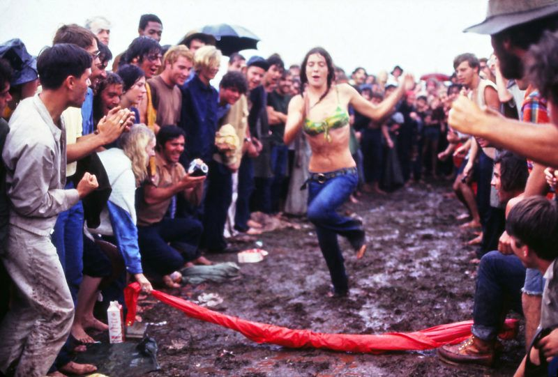 Woman running through the mud at the Woodstock Music Festival, New York, US, 17th August 1969. (Photo by Owen Franken/Corbis via Getty Images))