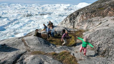 ILULISSAT, GREENLAND - JULY 30: Tourists walk on a rock overlooking the Ilulissat Icefjord on July 30, 2019 near Ilulissat, Greenland. As the Earth's climate warms summers have become longer in Ilulissat, allowing fishermen a wider period to fish from boats on open waters and extending the summer tourist season. Long term benefits are uncertain, however, as warming waters could have a negative impact on the local fish and whale population.  (Photo by Sean Gallup/Getty Images)