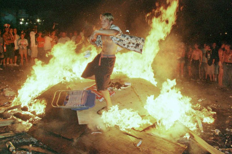 E 354866 001 25Jul99 Rome, New York A Young Man Dances In A Fire That Burns Into The Early Morning Hours Following The Close Of The Woodstock Music And Arts Festival In Rome, Ny, July 26. The Fans Are Burning Huge Plywood Panels That Had Been The Woodstock Peace Wall. The 30Th Anniversary Festival, Was Staged At The Former Griffiss Air Force Base.  (Photo By Joe Traver/Getty Images)