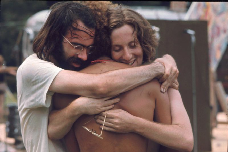 Three men attending the Woodstock music festival hug each other, Bethel, NY, August 1969. (Photo by Ralph Ackerman/Getty Images)