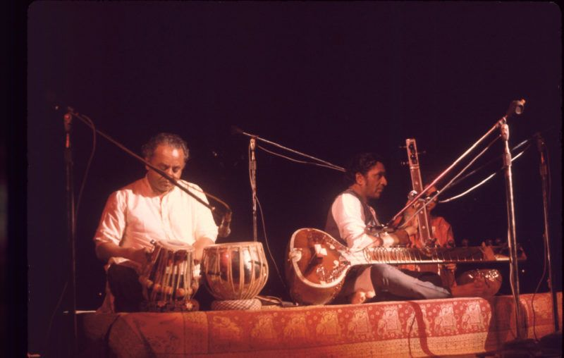 Indian musicians Ravi Shankar (center) and Alla Rakha (1919 - 2000) (left) perform on stage at the Woodstock Music and Arts Fair, Bethel, New York, August 15, 1969. With them, though partly obscured, is fellow musician Maya Kulkarni. The festival ran from August 15 to 18. (Photo by Ralph Ackerman/Getty Images)