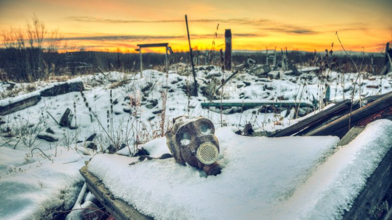 Nuclear winter.Old gas mask in the ruins. The remains of houses covered with snow at sunset