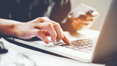 Man's hands typing laptop keyboard and holding credit card online shopping concept