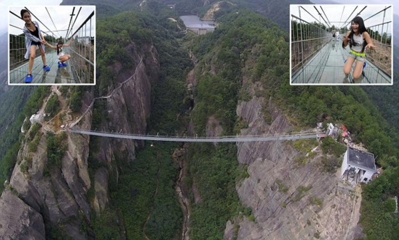 Mandatory Credit: Photo by Imaginechina/REX Shutterstock (5158442l)  Aerial view of the 180-meter-high and 300 meter-long glass-bottomed suspension bridge at the Shiniuzhai National Geopark in Pingjiang county, in central China's Hunan province, 24 September 2015.  Tourists visited a glass-bottomed suspension bridge that sits 180 metres above the ground at the Shiniuzhai National Geopark in Pingjiang county, in central China's Hunan province on Thursday (24 September 2015). The 300 metre-long suspended bridge, which apparently sways in the wind, spans a chasm at the national park, popular with tourists for its unique rock formations and geography. Walkers see clear, stomach-churning views of the ground 180 metres below. Park management authorities added a small section of glass last year but decided to transform the entire length of the crossing. The floor is made of a double layer of glass and is 24mm thick in total.  300 meter-long glass-bottomed suspension bridge opens in the Shiniuzhai National Geopark in Pingjiang, China - 24 Sep 2015  Tourists visited a glass-bottomed suspension bridge that sits 180 metres above the ground at the Shiniuzhai National Geopark in Pingjiang county, in central China's Hunan province on Thursday (24 September 2015). The 300 metre-long suspended bridge, which apparently sways in the wind, spans a chasm at the national park, popular with tourists for its unique rock formations and geography. Walkers see clear, stomach-churning views of the ground 180 metres below. Park management authorities added a small section of glass last year but decided to transform the entire length of the crossing. The floor is made of a double layer of glass and is 24mm thick in total.