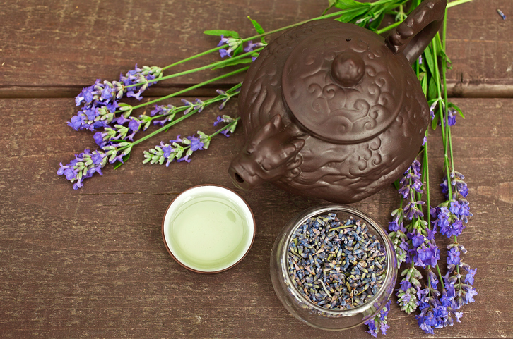 Lavender tea in a chinese clay teapot and a clay cup of lavender tea on a wooden table in the garden