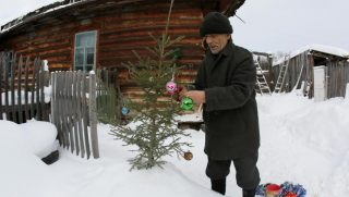 Mikhail Baburin, 66, decorates a fir tree for New Year and Christmas celebrations in front of his house in the remote Siberian village of Mikhailovka, Krasnoyarsk region, Russia. REUTERS/Ilya Naymushin