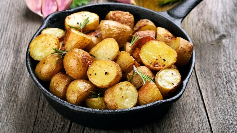 Roasted potato in frying pan on wooden background