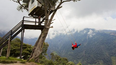 "Woman swinging at the famous swing at the ""End of the World"" located at the La Casa del Árbol (The Treehouse) in Baños, Ecuador."