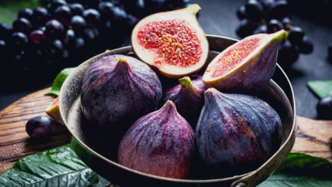 Fresh figs in vintage bowl on wooden board. Black grapes on background. Fruit plate
