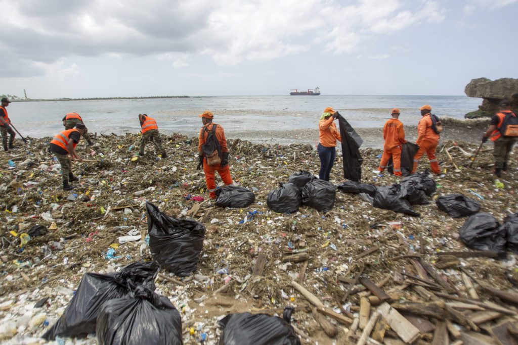 Workers from the Ministry of Public Works and Comunication (MOPC), collect garbage from the beaches of Güibia, Montesino and next to the female Obelisk in the Malecon area, in Santo Domingo on July 16, 2018. The MOPC started cleaning works to remove tons of solid waste from the coastline of the Malecon of Santo Domingo, after the subtropical storm Beryl passed over. / AFP PHOTO / Erika SANTELICES