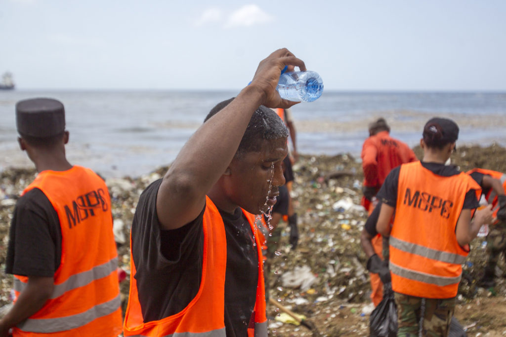 A worker from the Ministry of Public Works and Comunication (MOPC), throws water on his head during the garbage collect from the beaches of Güibia, Montesino and next to the female Obelisk in the Malecon area, in Santo Domingo on July 16, 2018. The MOPC started cleaning works to remove tons of solid waste from the coastline of the Malecon of Santo Domingo, after the subtropical storm Beryl passed over. / AFP PHOTO / Erika SANTELICES