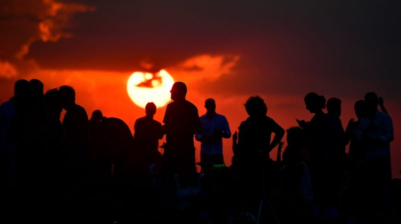 People gather as they wait for the sun to go down and the appearance of the 'Blood moon' in Berlin on July 27, 2018. The 'Blood moon' total lunar eclipse, is the longest of the 21st century. / AFP PHOTO / Tobias SCHWARZ