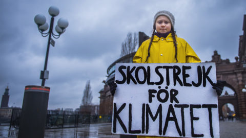 """Swedish 15-year-old girl Greta Thunberg holds a placard reading """"School strike for the climate"""" during a protest against climate change outside the Swedish parliament on November 30, 2018. - In more than hundred cities across Sweden, environmentalists have organised protests, partly inspired by Greta Thunberg, who strikes every Friday against climate change outside the parliament since several months. UN's annual climate talks which this year will take place in Poland starts on December 2, 2018. (Photo by Hanna FRANZEN / TT News Agency / AFP) / Sweden OUT"""