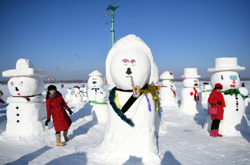 (190102) -- HARBIN, Jan. 2, 2019 (Xinhua) -- People pose for photo with snowman sculptures on the riverbank of Songhua River in Harbin, capital of northeast China's Heilongjiang Province, Jan. 2, 2019. Altogether 2,019 cute snowmen were displayed here to greet the year 2019. (Xinhua/Wang Jianwei)