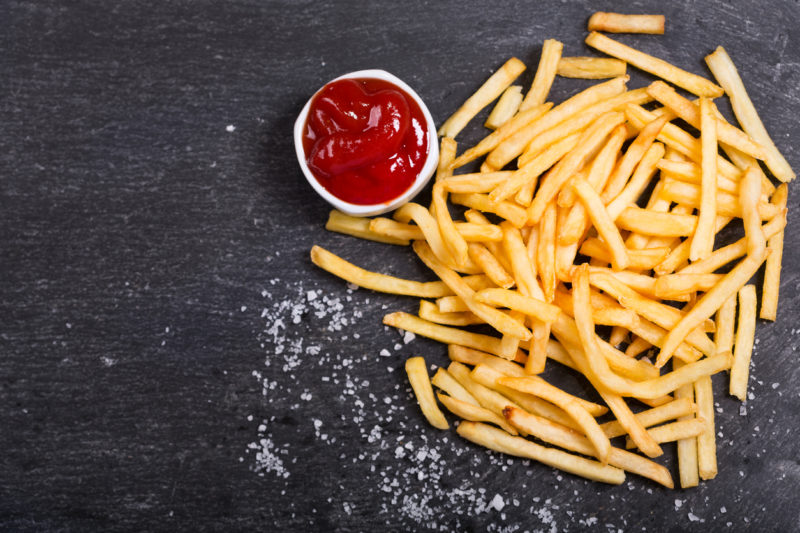 French fries with ketchup on dark table