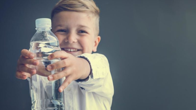 Close up of smiling boy holding plastic water bottle.