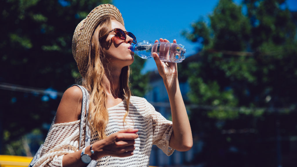 Profile of lovely woman in sunglasses, drinking a water, during walking outdoors. Dressed in trendy clothes, in hat. Summertime.