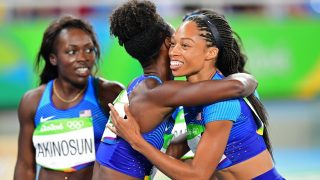 (FromL) USA's Morolake Akinosun, USA's Tianna Bartoletta and USA's Allyson Felix react after competing in the Women's 4 x 100m Relay Round 1 re-run during the athletics event at the Rio 2016 Olympic Games at the Olympic Stadium in Rio de Janeiro on August 18, 2016.   / AFP PHOTO / FRANCK FIFE