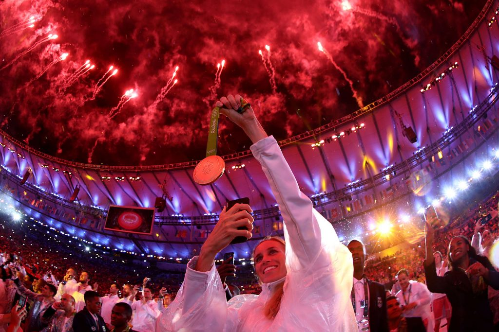 RIO DE JANEIRO, BRAZIL - AUGUST 21:  An athlete takes a photo of their medal as fireworks explode near the conclusion of the Closing Ceremony on Day 16 of the Rio 2016 Olympic Games at Maracana Stadium on August 21, 2016 in Rio de Janeiro, Brazil.  (Photo by Ezra Shaw/Getty Images)