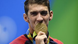 USA's Michael Phelps kisses his gold medal on the podium of the Men's 4x100m Freestyle Relay Final during the swimming event at the Rio 2016 Olympic Games at the Olympic Aquatics Stadium in Rio de Janeiro on August 7, 2016.   / AFP PHOTO / GABRIEL BOUYS