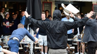 A Russia football supporter lobs a chair towards England fans sitting in a cafe in the northern city of Lille on June 14, 2016, three days after Russian and England supporters clashed in Marseille. A group of 43 Russian football supporters have been placed in custody in southern France and could appear in court over fan violence in Marseille, officials said June 14.  / AFP PHOTO / LEON NEAL
