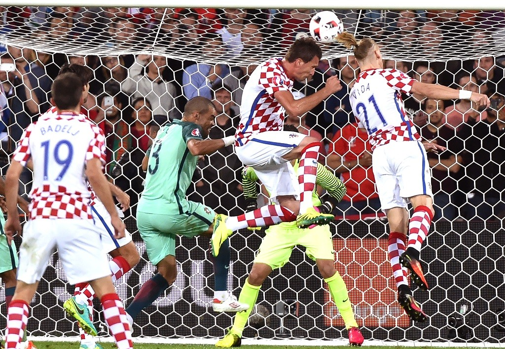 Portugal's defender Pepe (2nd L) vies with Croatia's defender Domagoj Vida (R) and Croatia's forward Mario Mandzukic (2nd R) during the Euro 2016 round of sixteen football match Croatia vs Portugal, on June 25, 2016 at the Bollaert-Delelis stadium in Lens. / AFP PHOTO / PHILIPPE HUGUEN