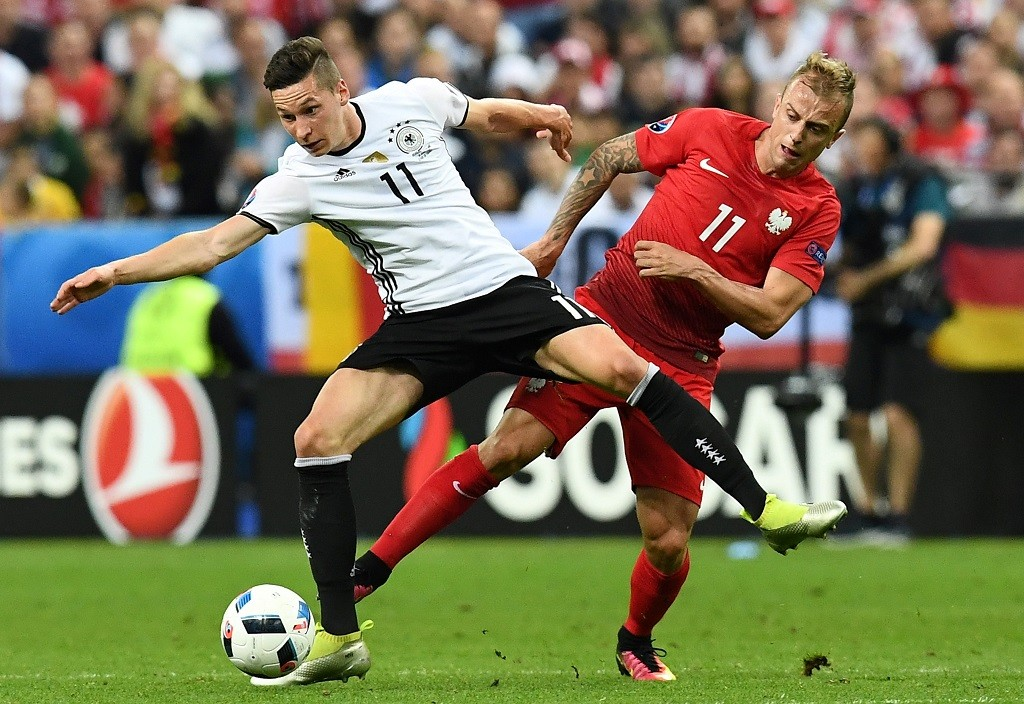 Germany's midfielder Julian Draxler vies for the ball against Poland's midfielder Kamil Grosicki during the Euro 2016 group C football match between Germany and Poland at the Stade de France stadium in Saint-Denis near Paris on June 16, 2016. / AFP PHOTO / FRANCK FIFE