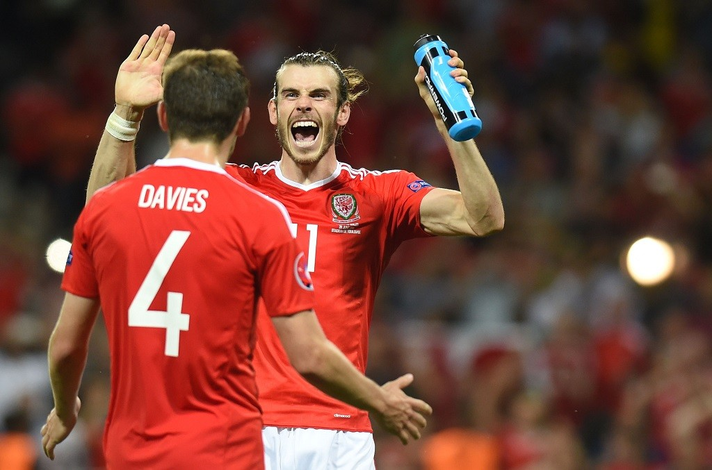 Wales' forward Gareth Bale celebrates with Wales' defender Ben Davies the team's 3-0 win in the Euro 2016 group B football match between Russia and Wales at the Stadium Municipal in Toulouse on June 20, 2016. / AFP PHOTO / Rémy GABALDA