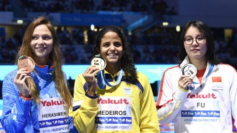 Gold medalist Brazil's Etiene Medeiros (L), silver medalist China's Fu Yuanhui (R) and bronze medalist Belarus' Aliaksandra Herasimenia celebrate on the podium of the women's 50m backstroke event during the swimming competition at the 2017 FINA World Championships in Budapest, on July 27, 2017.  / AFP PHOTO / CHRISTOPHE SIMON
