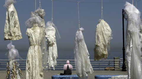 A veiled woman sits on a bench near an installation of wedding dresses by Lebanese artist Mireille Honein and Abaad NGO at Beirut's Corniche, on April 22, 2017, denouncing the article 522 of Lebanon's penal code allowing rapists who marry their victims to go free.A proposal to scrap the article was introduced last year and approved by a parliamentary committee in February, but it must now be voted on by the full legislative body. / AFP PHOTO / PATRICK BAZ / RESTRICTED TO EDITORIAL USE, MANDATORY MENTION OF THE ARTIST UPON PUBLICATION, TO ILLUSTRATE THE EVENT AS SPECIFIED IN THE CAPTION