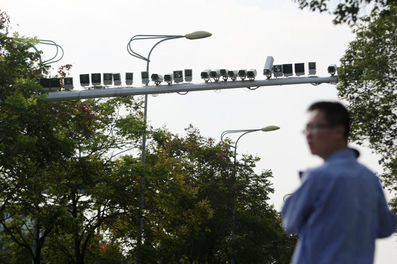 A pedestrian walks past dozens of surveillance cameras and flashes installed on a beam over a road in Shanghai, China, 5 November 2013.Surveillance cameras have gone hot in China these days not only because public concerns rise over their normal operation in heavy smog but also as more than 50 cameras and flashes were found on the two sides of a beam over a road in Shanghai, shocking and frightening Chinese drivers. The surveillance lineup was installed near a crossroad in the citys Baoshan District. Each side of the beam is equipped with more than 20 cameras and flashes over one side of the 6-lane Youyi Road. Many netizens doubted the effect of so many cameras on one single beam and criticized the local traffic police department for wasting money of taxpayers.