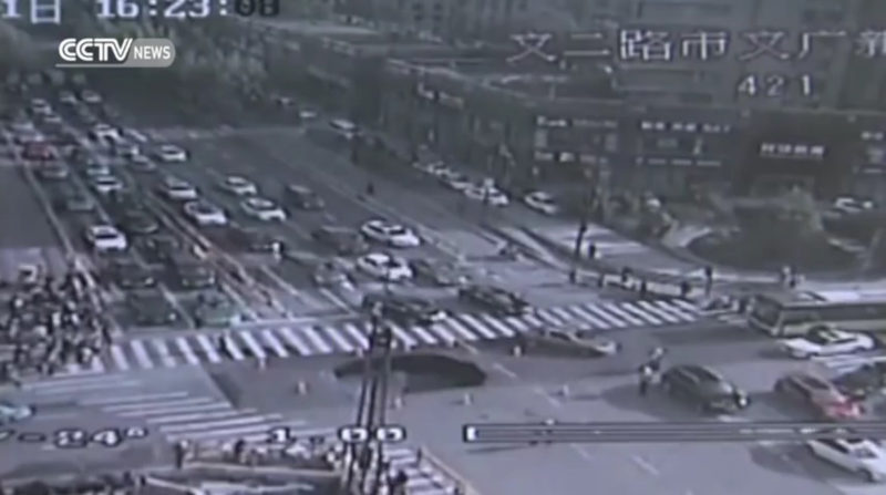 In this screen shot of a surveillance camera footage, the road surface collapses to create a sinkhole following the cave-in at a crossing in Hangzhou city, east China's Zhejiang province, 21 April 2016.Li Weiqi, a 40-year-old auxiliary traffic police officer in Hangzhou, Zhejiang province, has become a household name after a surveillance video was broadcast showing how he prevented what might have been a major tragedy last week at a busy intersection in the city. Li, who is originally from northeast China's Liaoning province, has served as a member of Hangzhou's West Lake detachment of the Traffic Management Bureau since March 2015. Traffic monitoring cameras caught the moment on April 21, 2016 when he noticed something wrong with the road after seeing cracks that everybody else was ignoring. Li immediately recognized the danger and stopped traffic before directing drivers away from the buckling road surface. Three minutes later, the crack widened and developed into a 20-square-meter sinkhole that was 2 meters deep. The hole could have easily swallowed three cars. Commentators said it was due to Li's quick thinking that no one was injured. His quick response became known immediately after the incident when media coverage started by domestic and major western media outlets, including the Cable News Network in the US. CNN uploaded the video to its Facebook page and has received more than 3.6 million clicks and about 20,000 reposts so far. On Wednesday (27 April 2016), the city's government nominated Li for a first-class public security award. Li said he is paid more than 2,000 yuan ($300) a month and works 10 hours a day, which has triggered a debate on the internet about whether contract workers like Li should be paid something closer to the earnings of regular traffic police, who earn around 8,300 yuan a month.