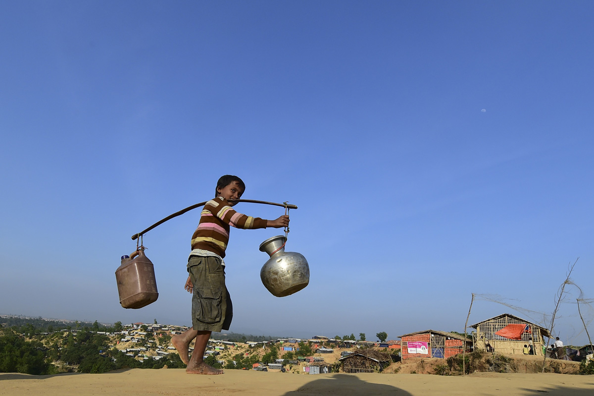 """A Rohingya refugee child walks back to his makeshift shelter after collecting water at Hakimpara refugee camp in Bangladesh's Ukhia district on January 27, 2018.The repatriation of hundreds of thousands of Rohingya Muslims who fled violence in Myanmar will not begin as planned, Bangladesh said January 22, with authorities admitting """"a lot of preparation"""" was still needed. / AFP PHOTO / Munir UZ ZAMAN"""