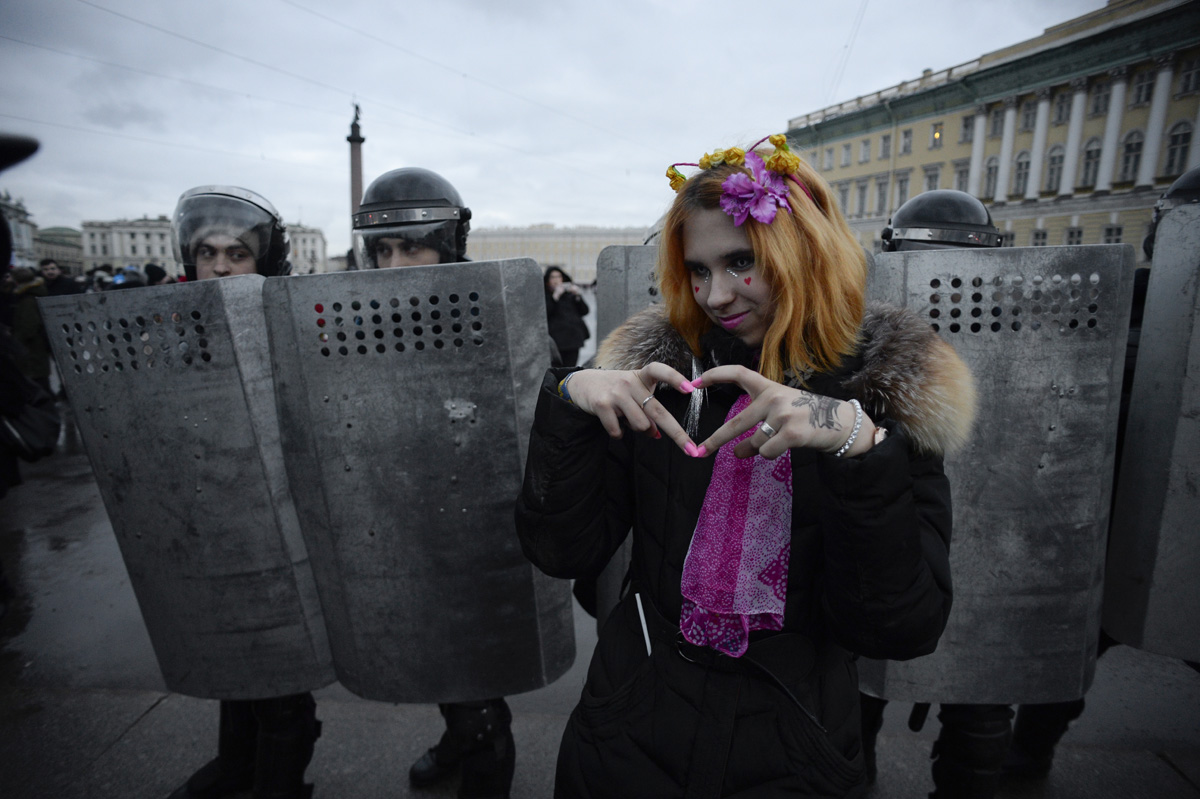 A woman gestures in front of riot police during a rally calling for a boycott of March 18 presidential elections, Saint Petersburg, January 28, 2018. / AFP PHOTO / OLGA MALTSEVA
