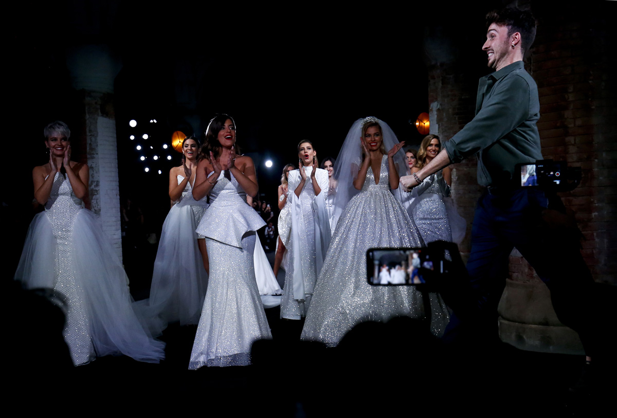 Models applaud as Spanish designer Jose Maria Garcia (R) appears on the catwalk following the presentation of Ze Garcia collection during the 080 Barcelona Fashion Week in Barcelona on January 29, 2018. / AFP PHOTO / PAU BARRENA