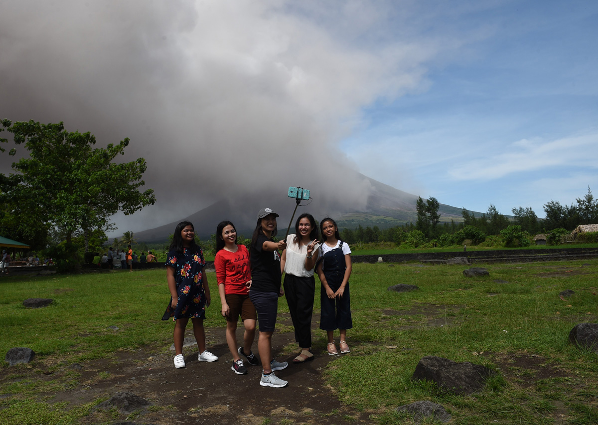 """Local tourists take selfie as Mayon volcano spews ash at Cagsawa ruins in Daraga town, Albay province, south of Manila on January 30, 2018. With chili-flavoured """"lava ice cream"""" in demand and awestruck tourists packing onto viewing decks, the erupting Mayon volcano is sparking a local business boom in an impoverished region of the Philippines where tens of thousands of others have fled for their lives. / AFP PHOTO / TED ALJIBE"""