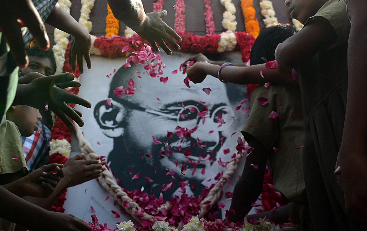 Indian school children pay homage to a portrait of Indian independence icon Mahatama Gandhi, on Martyr's Day to mark the 70th anniversary of Gandhi's assassination, in Chennai on January 30, 2018.Gandhi was on the way to a prayer meeting in the Indian capital when he was shot three times in the chest and head on January 30, 1948. / AFP PHOTO / ARUN SANKAR