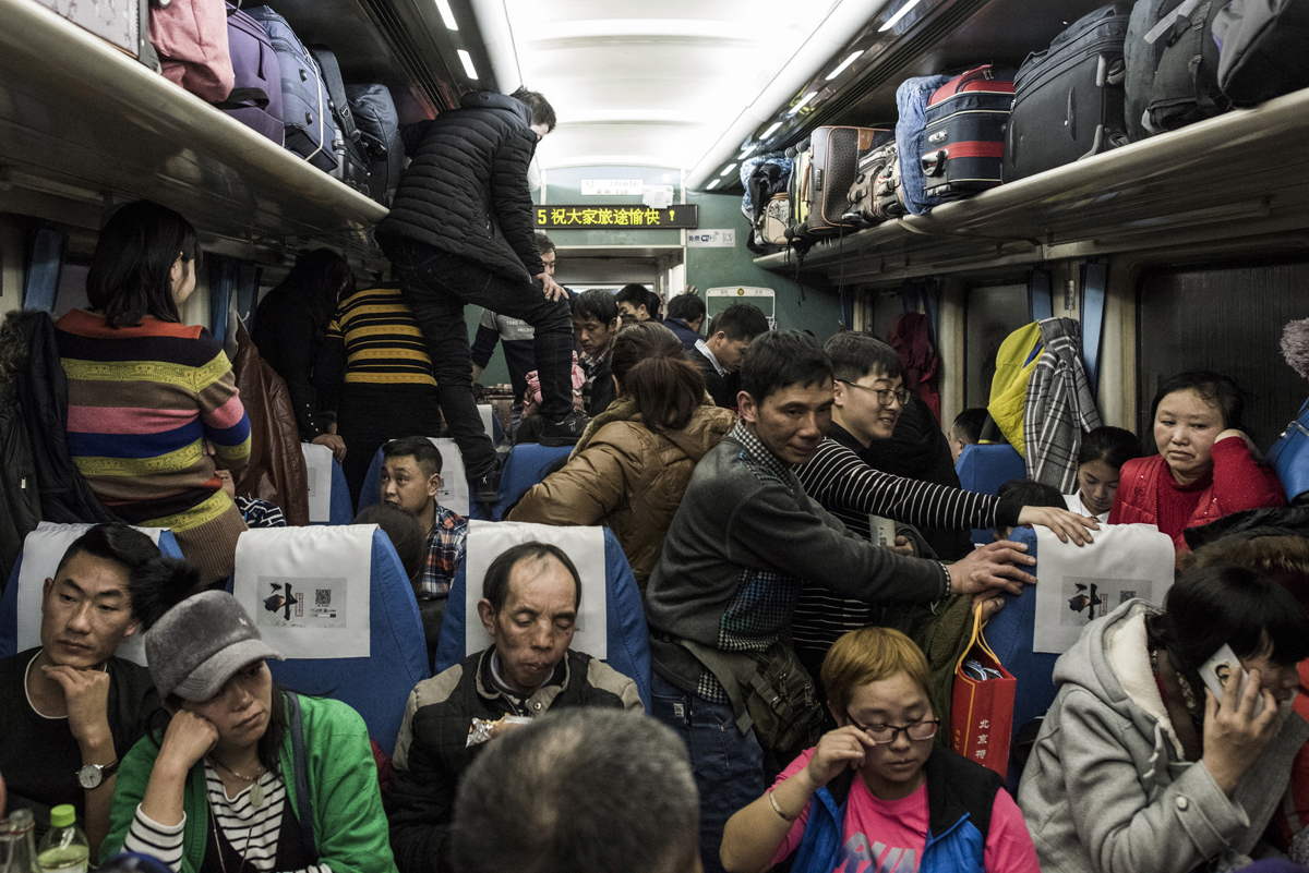This photo taken on February 10, 2018 shows passengers travelling on a crowded train during the 26-hour journey from Beijing to Chengdu, in Shijiazhuang, as they head home ahead of the Lunar New Year.China is in the midst of its annual travel rush as millions head to their hometowns to enjoy a week-long holiday. The Lunar New Year begins on February 16, and authorities expect more than 390 million train trips to take place between February 1 and March 12. / AFP PHOTO / FRED DUFOUR / TO GO WITH China-NewYear-migration-transport,FOCUS by Joanna Chiu and Fred Dufour