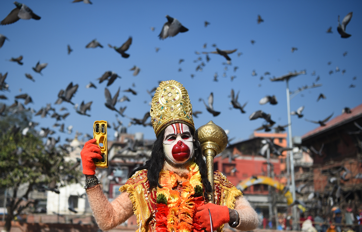 A Hindu Sadhu (holy man) dressed as Hanuman the monkey god, poses ahead for a picture ahead of the forthcoming Hindu festival of 'Maha Shivaratri' at the Pashupatinath temple in Kathmandu on February 11, 2018. Hindus mark the 'Maha Shivratri' festival by offering special prayers and fasting, with sadhus arriving at Pashupatinath to take part in the event, which takes place on February 13. / AFP PHOTO / PRAKASH MATHEMA