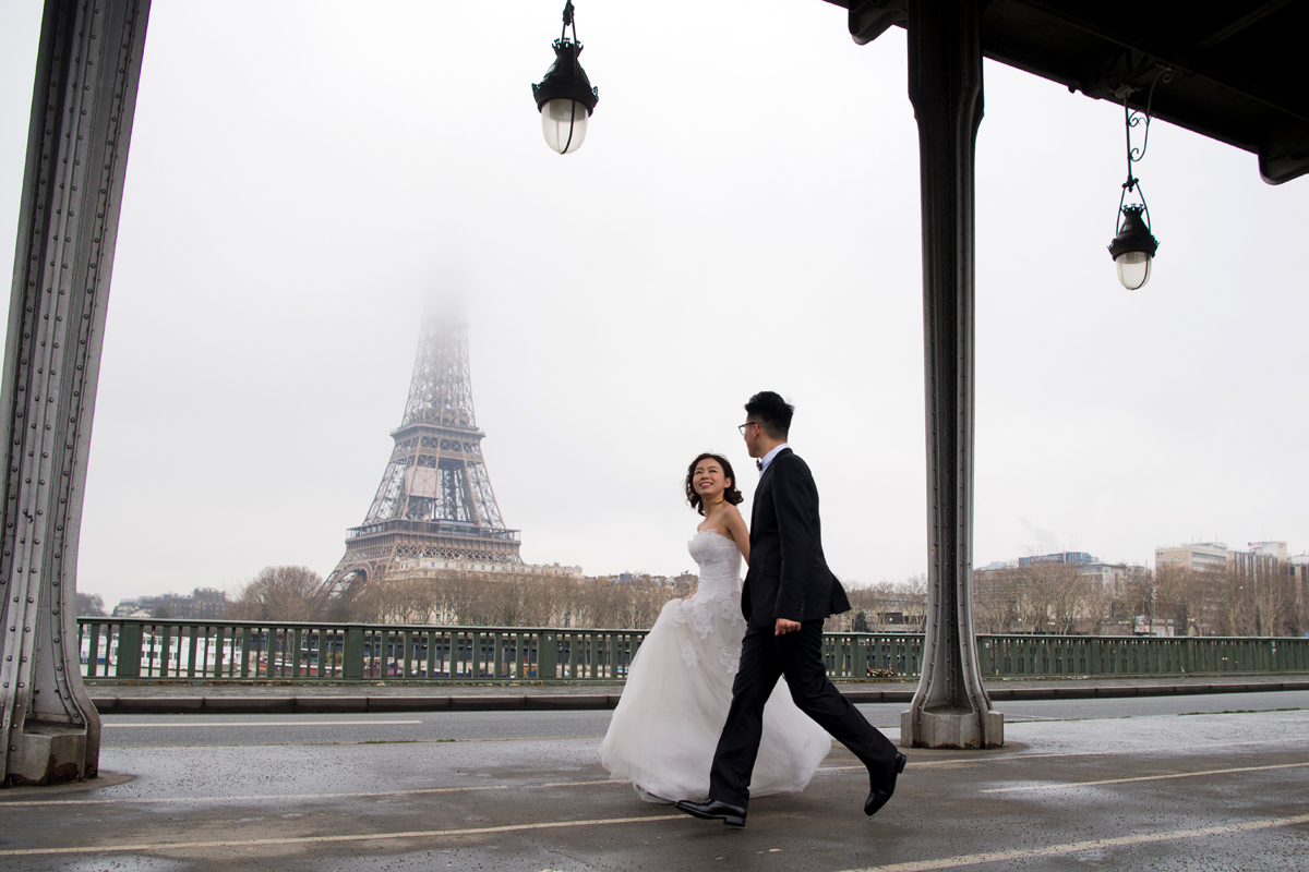 A couple in wedding dress and gown walks on the Pont de Bir-Hakeim bridge, with the Eiffel Tower in the background, on Valentine's Day, February 14, 2018 in Paris. / AFP PHOTO / ALAIN JOCARD