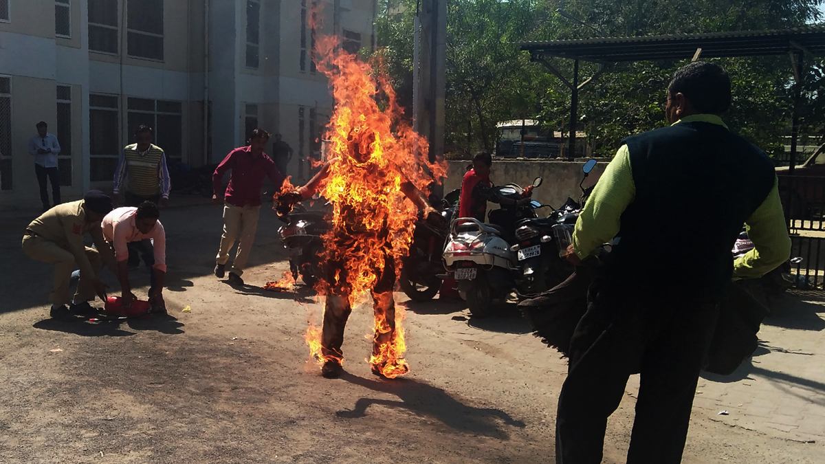 Indian police officials begin efforts to save Bhanubhai Vankar, who set himself on fire outside the Patan district collector's office  at Patan town, some 100 kms. from Ahmedabad on February 15, 2018. Vankar, a Dalit by caste set himself on fire alleging a delay in the handing over of a piece of land allotted to him under a government scheme in Patan town. / AFP PHOTO / -