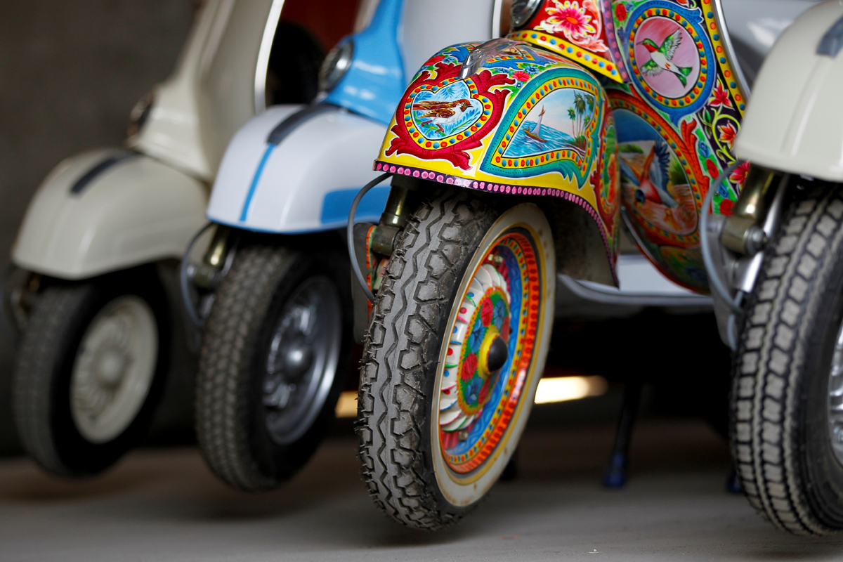 """A restored Vespa scooter painted in Pakistani truck art style, is parked alongside traditionally-coloured scooters at a Vespa restoration and repair workshop in Islamabad, Pakistan February 27, 2018. REUTERS/Caren Firouz  SEARCH """"VESPA PAKISTAN"""" FOR THIS STORY. SEARCH """"WIDER IMAGE"""" FOR ALL STORIES."""