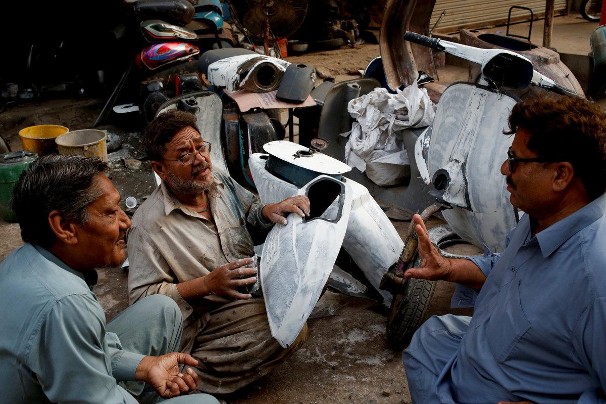"""Akram (C) applies coating on Vespa scooter parts, as he chats with owners of Vespa scooters Farrukh Shahbaz (L) and Matiur Rehman outside his workshop in Karachi, Pakistan February 24, 2018. Shahbaz, who, 14 years ago, inherited his father's blue 1961 Vespa, has had to have the scooter repaired three times, but he cherishes the memory and love his father had for the machine. """"My father told me it came packed in a wooden box,"""" said Shahbaz, 50. REUTERS/Akhtar Soomro  SEARCH """"VESPA PAKISTAN"""" FOR THIS STORY. SEARCH """"WIDER IMAGE"""" FOR ALL STORIES."""