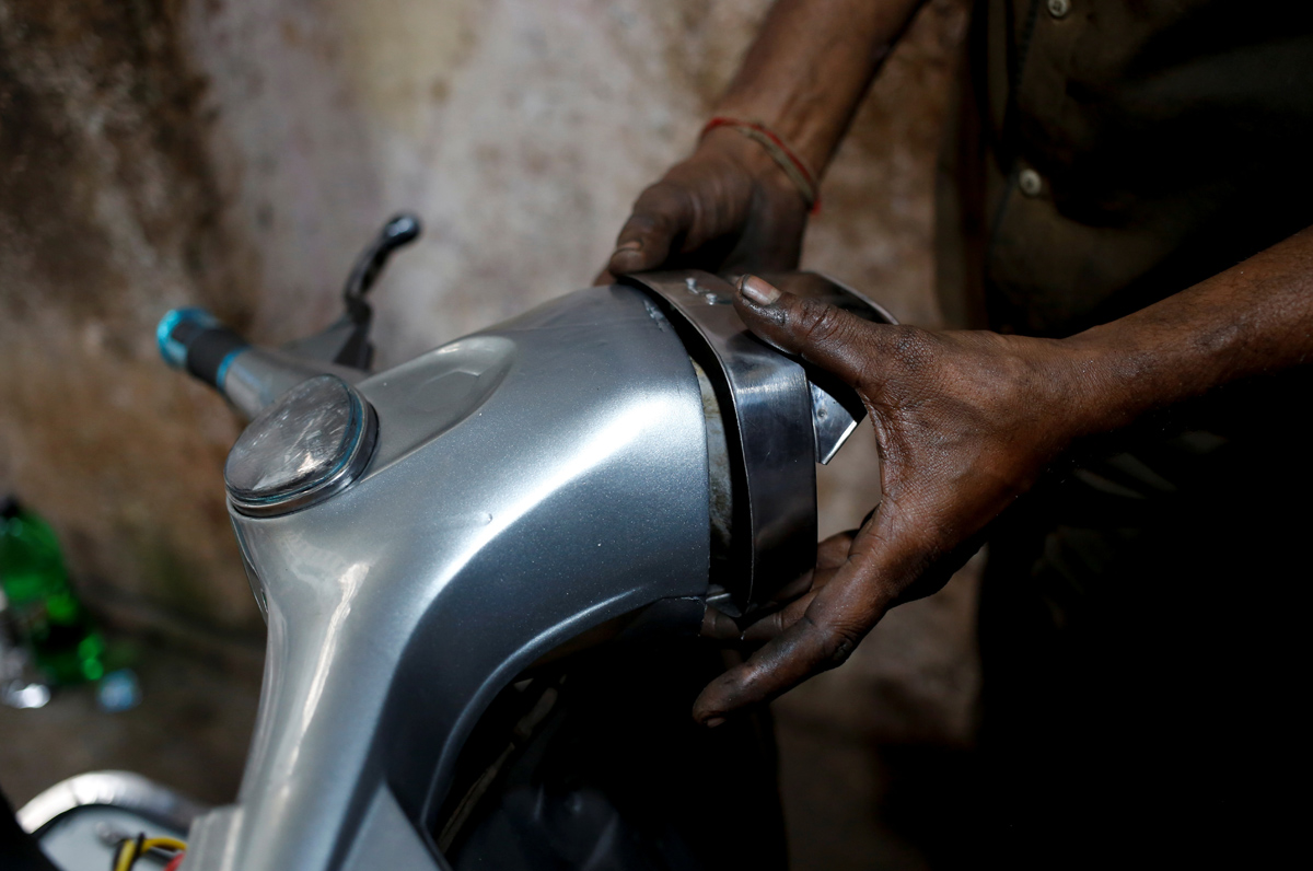 """A mechanic puts a headlight on a Vespa scooter, after repairing it at a workshop in Karachi, Pakistan March 1, 2018. REUTERS/Akhtar Soomro  SEARCH """"VESPA PAKISTAN"""" FOR THIS STORY. SEARCH """"WIDER IMAGE"""" FOR ALL STORIES."""