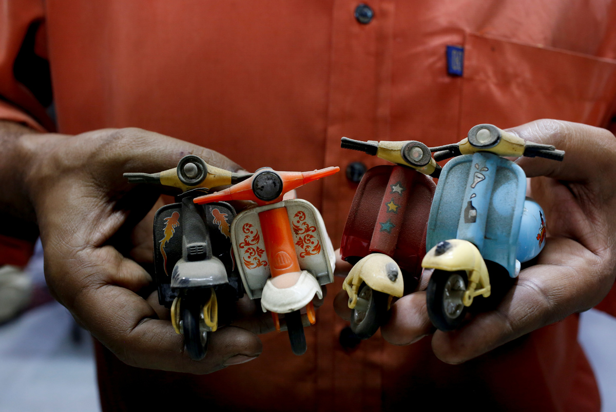 """A shopkeeper and Vespa enthusiast holds his collection of mini memorabilia, at his auto parts shop in Karachi, Pakistan February 28, 2018. REUTERS/Akhtar Soomro  SEARCH """"VESPA PAKISTAN"""" FOR THIS STORY. SEARCH """"WIDER IMAGE"""" FOR ALL STORIES."""
