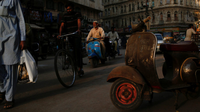 """A man rides a Vespa scooter on a busy street, in a low-income neighbourhood in Karachi, Pakistan March 6, 2018. REUTERS/Akhtar Soomro  SEARCH """"VESPA PAKISTAN"""" FOR THIS STORY. SEARCH """"WIDER IMAGE"""" FOR ALL STORIES."""
