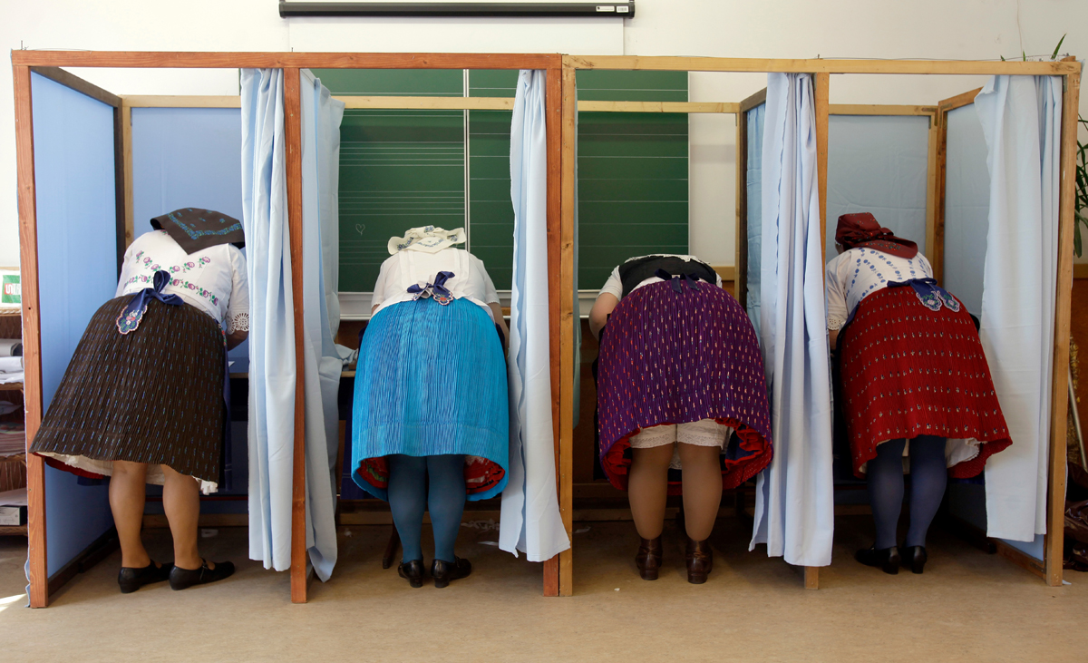 Women dressed in traditional Hungarian outfit prepare their votes in a polling station in a school in Veresegyhaz, some 30kms east of Budapest, on April 8, 2018, during the general election. 