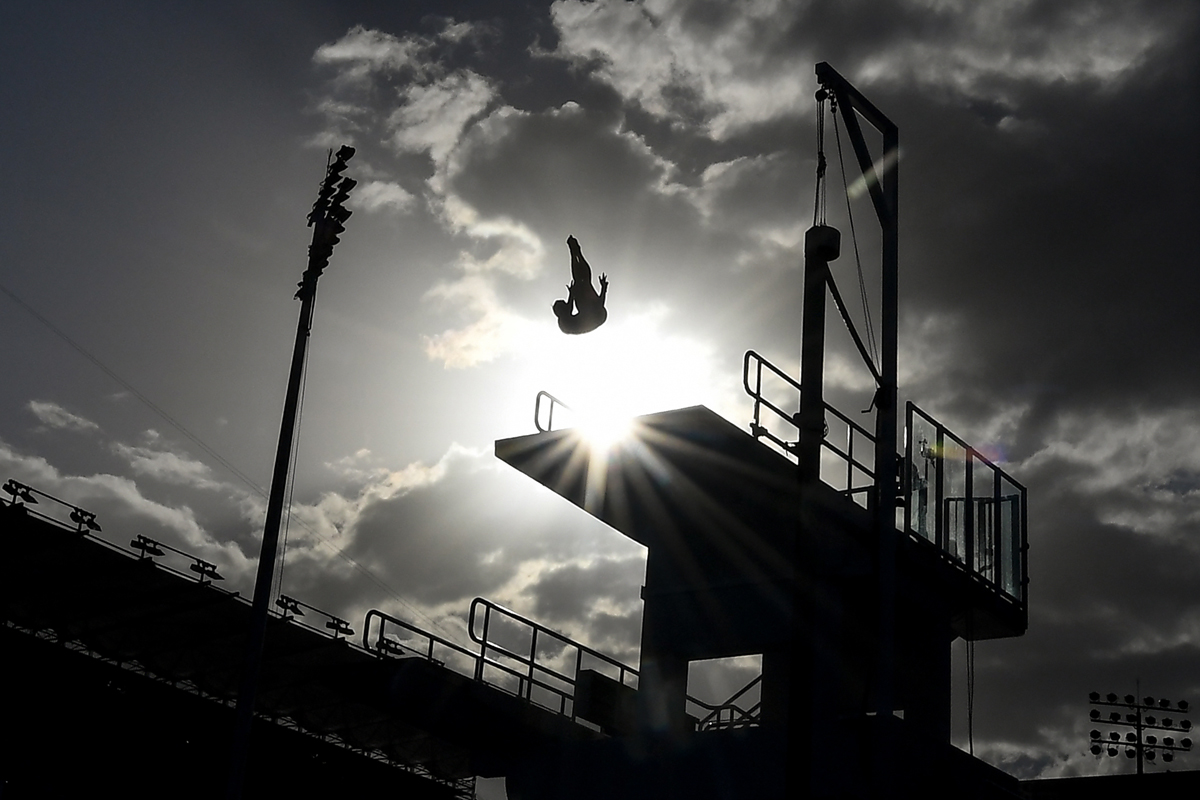 Silhouettes of athletes as they take part in a training session during the 2018 Gold Coast Commonwealth Games at the Optus Aquatic Centre in the Gold Coast on April 10, 2018. / AFP PHOTO / Manan VATSYAYANA