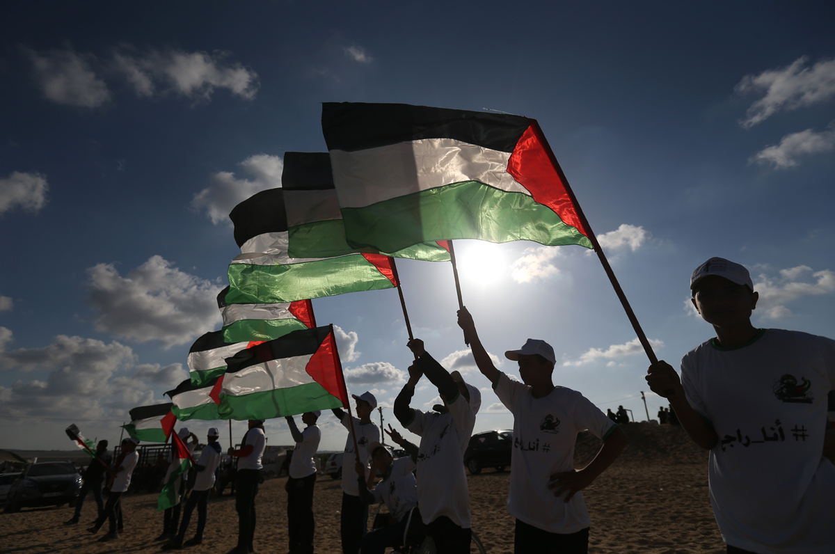 Palestinians hold their national flag on April 10, 2018 at the site of protests on the Israel-Gaza border east of Jabalia in the northern Gaza Strip. 
