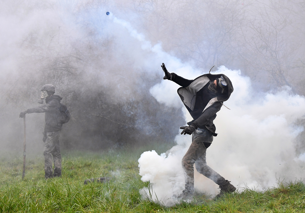 A protester throws a teargas canister towards riot forces as clashes erupt during a police operation to raze the decade-old camp known as ZAD (Zone a Defendre - Zone to defend) at Notre-Dame-des-Landes, near the western city of Nantes on April 10, 2018, and evict the last of the protesters who had refused to leave despite the government agreeing to ditch a proposed airport.
